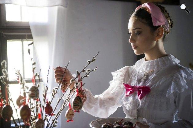Egy népviseletbe öltözött lány húsvétfa állítása (MTI Fotó)